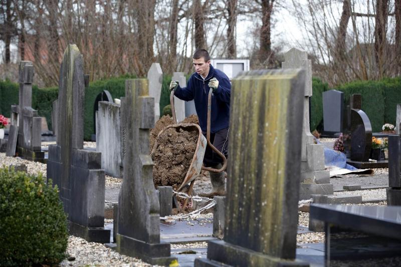 Werner Weijkamp van het Gelders Genootschap voert voor de gemeente Wijchen een inventarisatie uit van begraafplaatsen.  op de begraafplaats staat ook nog een 'knekelhuisje'.  Adriaan Strik (85) loopt ook mee.. Batenburg, 11-12-2014 . dgfoto.