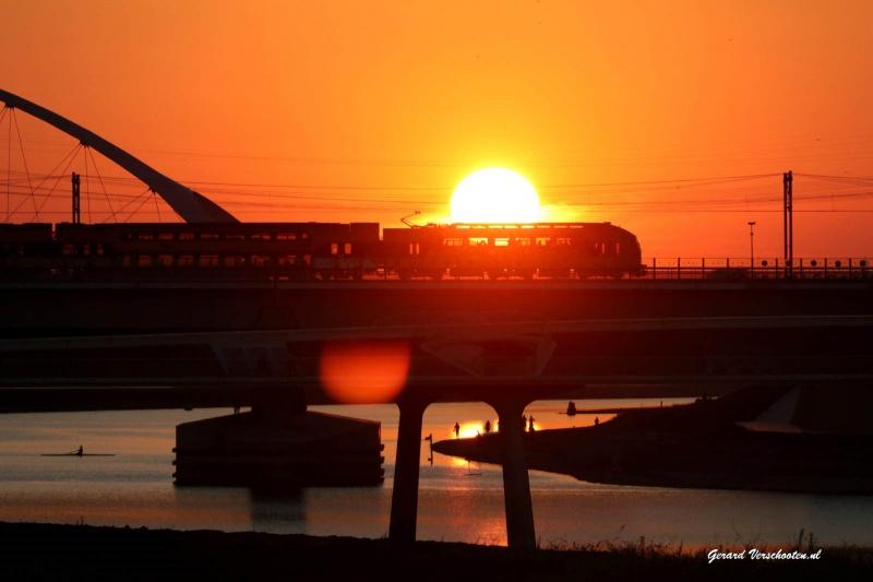Ondergaande zon met brug, trein, centrale. Nijmegen, 26-8-2016 .