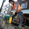 Verwijderen Bloembak voor de Plak met afbouwhamer Simone en Geertje en Michelle kijken toe