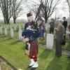 Eunice Ferguson bij graf broer militair kerkhof Zevenheuvelen met doedelzakspeler